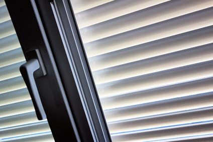 Zum Schutz gegen Hitze und Sonne werden an einem Fenster Jalousien angebracht.